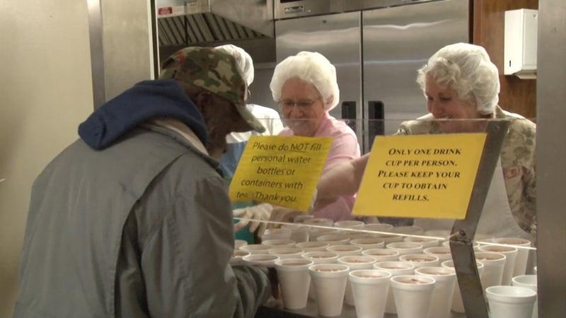 Volunteers serving a homeless man a sweet tea.