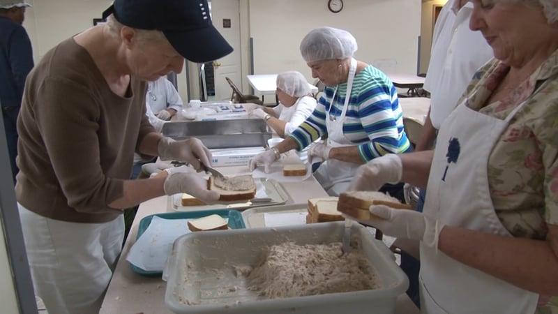 Volunteers preparing chicken salad sandwiches.
