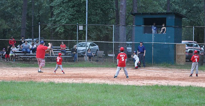 The Trenholm Globetrotters get ready to make a defensive play as a Trenholm Fireballs player prepares for the pitch. The Globetrotters won 13-2 against the Fireballs.