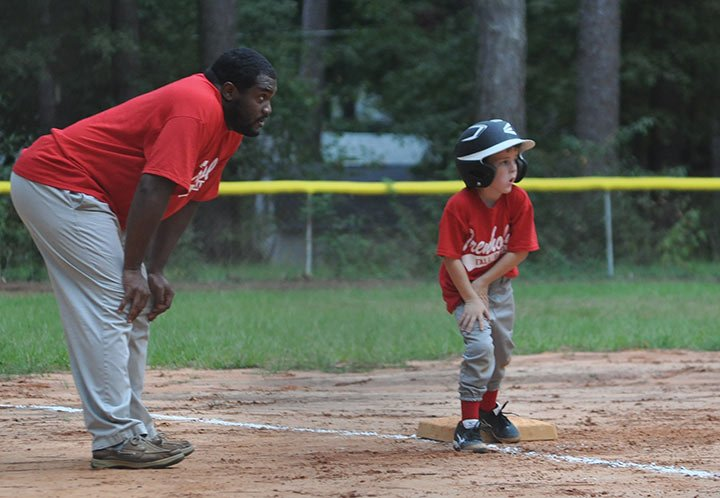 Coach Rickey Fruster, left,  and Gabe Ingram Jr. wait for a team hit, so Ingram can score one of their team's 13 runs during their double-digit victory at Trenholm Park.