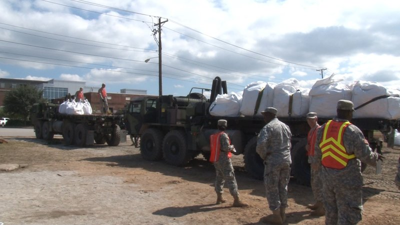 Soldiers work together to load sandbags to build dam.