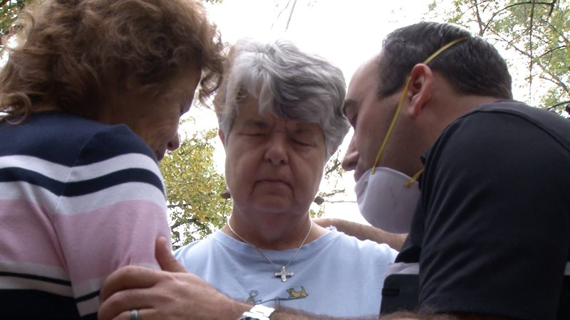 Dan Moore prays with Jan and a volunteering neighbor.