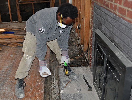 Brenton Lowe, a volunteer with AmeriCorps, helps gut the inside of Kenneth Styer's home after flooding ruined the structure of the house.
