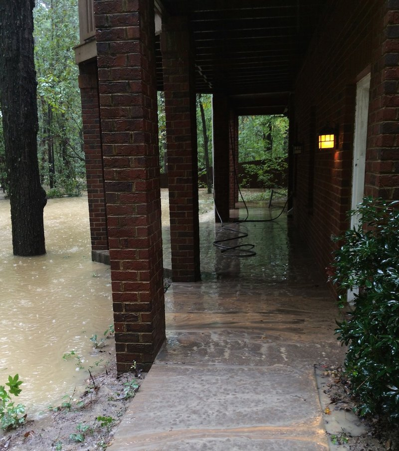 Flood water rested on the back patio with electrical wires dangling from the ceiling.