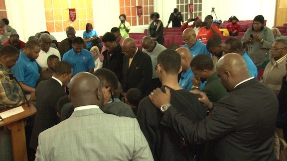 All men in the church circled around the young boys to pray that they would grow up without knowing violence.