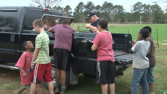 A group of boys help their house parent wash his truck.