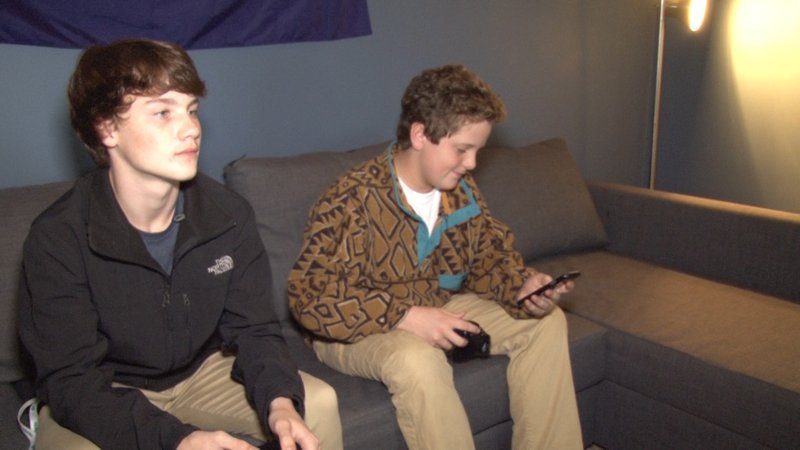 Graham Jacobson plays video games with a friend while checking text messages on his phone