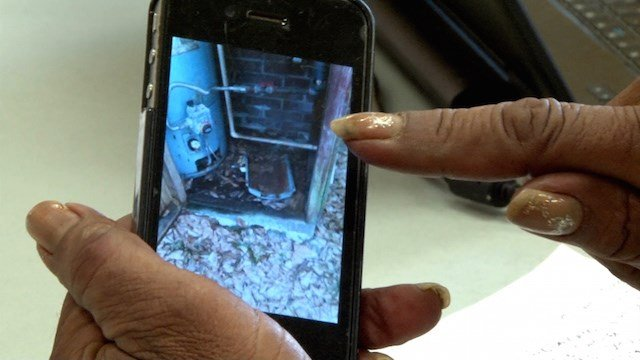 Richland County resident Debra Abraham shows pictures of her broken water heater and failed septic system.