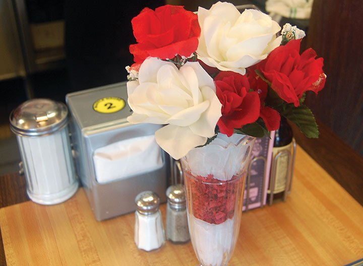 Bouquets of flowers are set on each cloth lined table for the romantic dinner Waffle House offers. The manager says sometimes the men will come in early and bring their own flowers and gifts for their ladies.