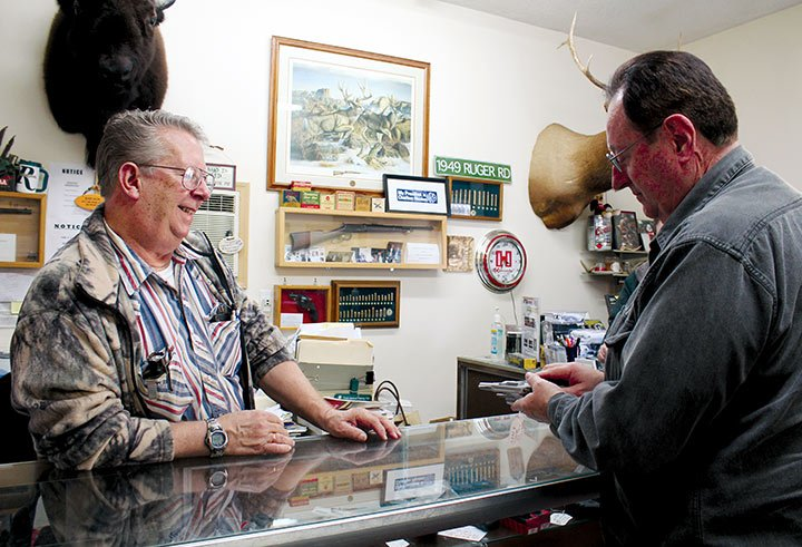 """Gerald Stoudemire and long-time customer Robert Messengers look at a .38 caliber revolver. Stoudemire opposes registering firearms through SLED, an idea recently proposed in legislature. """"There is no way this state can afford that,"""" he said."""